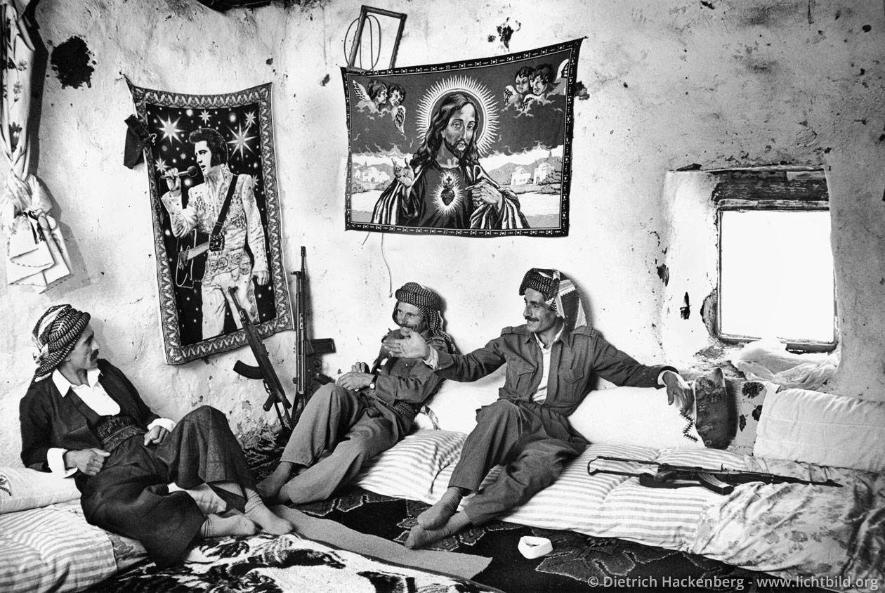 Kurdische Dorfwächter - Beytüssebap, Provinz Hakkari, Türkei 1991 An der Wand Teppiche mit Elvis und Jesus. Türkisch Kurdistan 1991. Foto © Dietrich Hackenberg