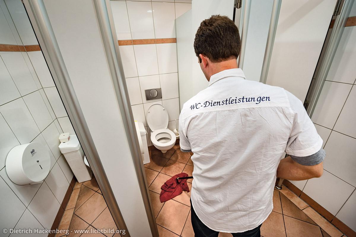 WC-Dienstleistungen steht auf dem Hemd von Torsten, der gerade einmal durchwischt. Arbeitsplatz Toilette - Kaufhof Dortmund - Foto © Dietrich Hackenberg