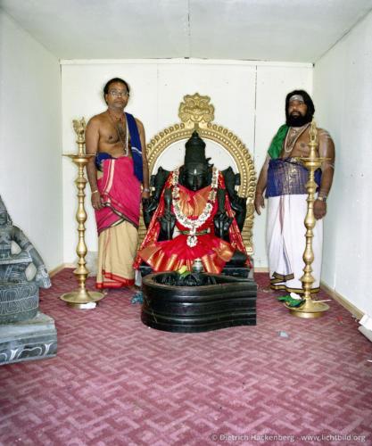 Priester und Tempeldiener neben der Göttin Sri Kamadschi Ampal - Hindutempel, Hamm-Uentrop - Bis zur Fertigstellung des Tempel steht die Göttin in einem Container. Foto © Dietrich Hackenberg
