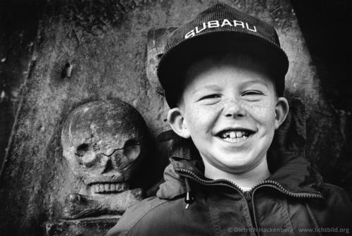 Sommersprossen und Totenkopf - Miltenberg, Bayern - Amerikanischer Touristenjunge vor einem alten Grabstein Sommersprossen und Totenkopf - Foto © Dietrich Hackenberg