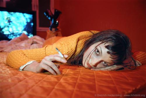 """Junge Frau auf Bett - Standbild für den Film """"Das Phantom"""" Berlin-Mahrzahn - Foto © Dietrich Hackenberg"""